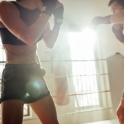 Male boxer trains with muscular woman in shorts as the sun shines in through nearby windows