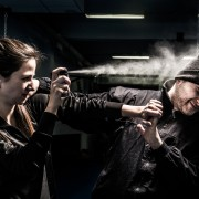 The young woman is defending herself from an attacker. Mixed pair demonstrates using of a pepper spray for self defense. The attacker - a young man, wearing a black jacket and knit cap.